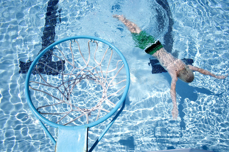 Young boy in swimming pool with hoop in foreground stock photo
