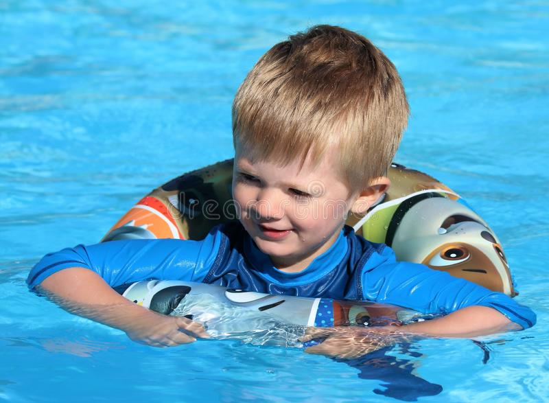 Young boy in the swimming pool with a rubber ring. Happy young lad swimming in a pool with a rubber ring buoyancy aide stock photos