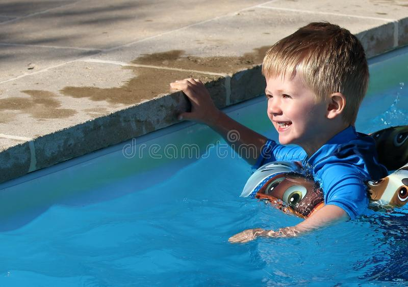 Young boy in the swimming pool with a rubber ring. Happy young lad swimming in a pool with a rubber ring buoyancy aide holding on to the edge stock photo