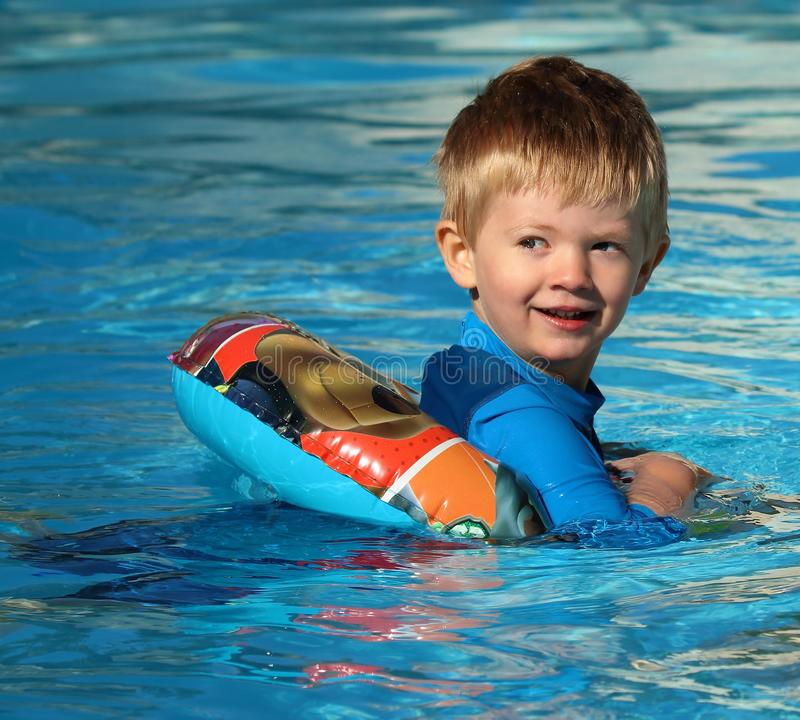 Young boy in the swimming pool with a rubber ring. Happy young lad swimming in a pool with a rubber ring buoyancy aide looking back over his shoulder stock photos
