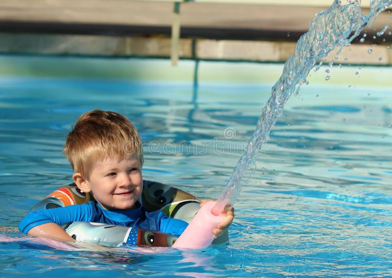 Young boy in the swimming pool with a rubber ring and a water spout. Happy young lad swimming in a pool with a rubber ring buoyancy aide and a water fountain stock photos