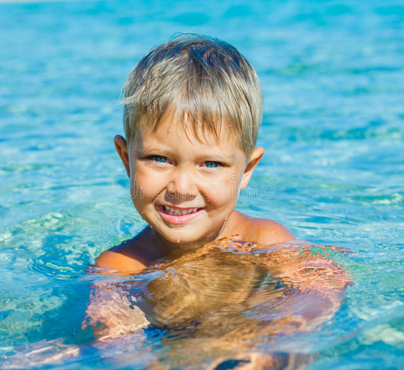 Young boy swimming in sea. Portrait of young boy swimming in the transparent sea stock photos