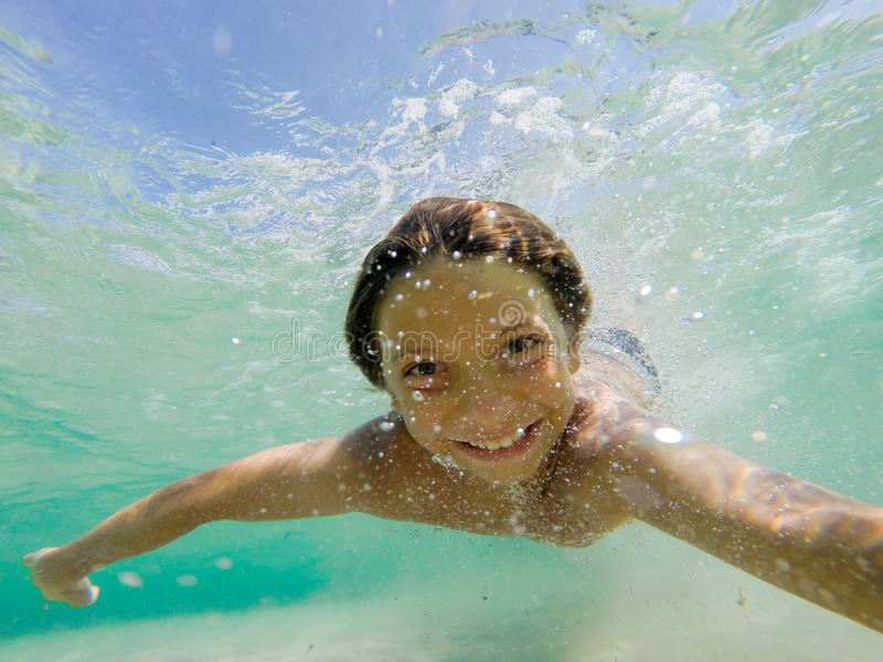Young boy swimming underwater. In tropical sea stock photo
