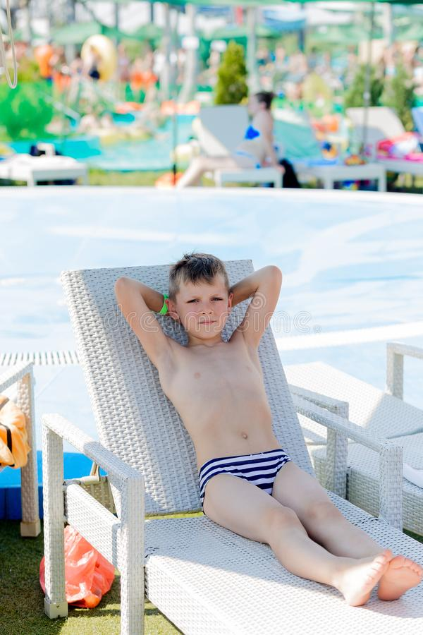 Young boy in a swimsuit on a shelf by the pool royalty free stock image