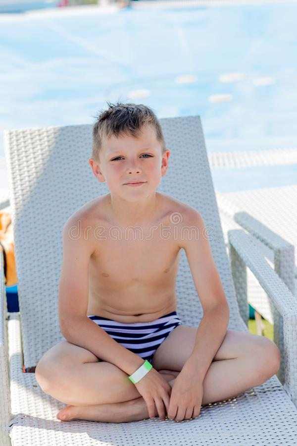 Young boy in a swimsuit on a shelf by the pool stock image