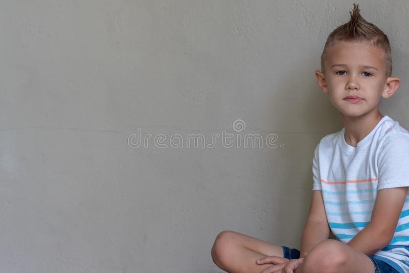 Young boy in t shirt posing, wall behind, copy space stock images
