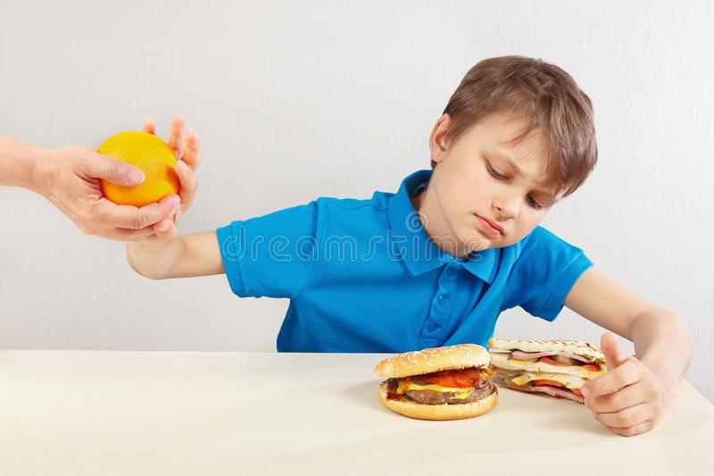 Young boy at the table chooses between fastfood and fruits on white background stock image