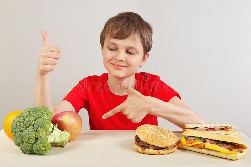 Young boy at the table chooses between fastfood and healthy diet on white background stock images