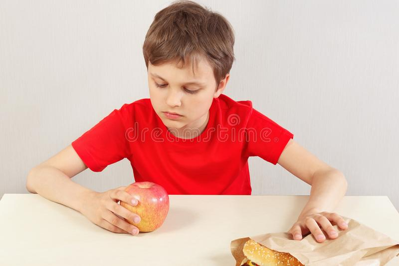 Young boy at the table chooses between hamburger and apple on white background royalty free stock image