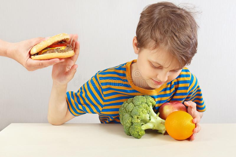 Young boy at the table refuses hamburger in favor of fruit and vegetables. On a white background stock photos