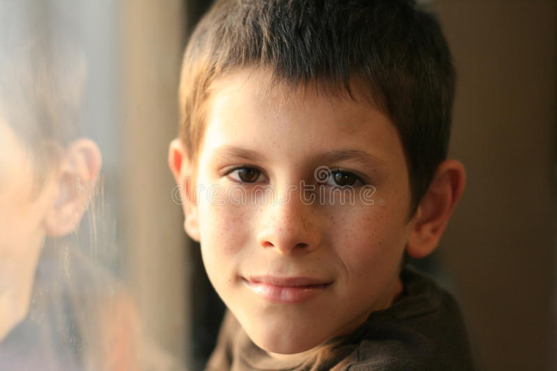Young boy in thought with window reflection. Contemplating young boy in thought with window reflection stock image
