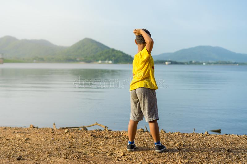 Young boy throw stone into the water at Bang Pra Reservoir in sunset.  royalty free stock photography