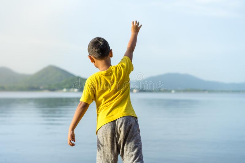 Young boy throw stone into the water at Bang Pra Reservoir in sunset.  royalty free stock photos