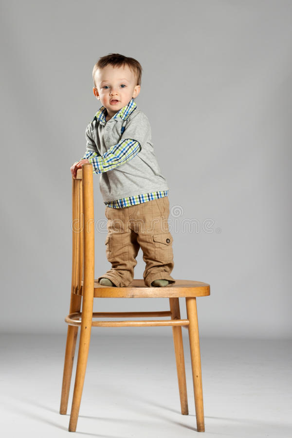 Young boy toddler. Toddler boy standing on a big wooden chair stock images