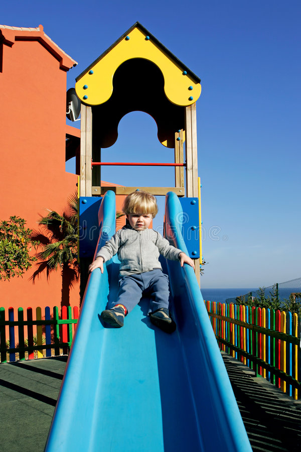 Young boy or toddler coming down a slide in the sun royalty free stock photos