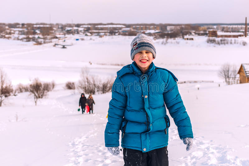 Young boy on top of a snowy river Bank royalty free stock photography