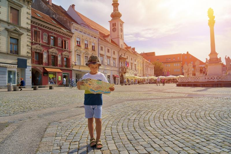 Young boy tourist with city map stay on the old european street royalty free stock images