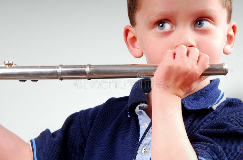 Young Boy Trying To Play Flute Royalty Free Stock Photography