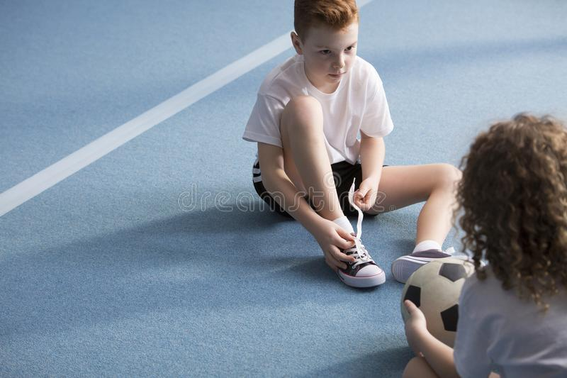 Young boy tying sport shoes royalty free stock photo