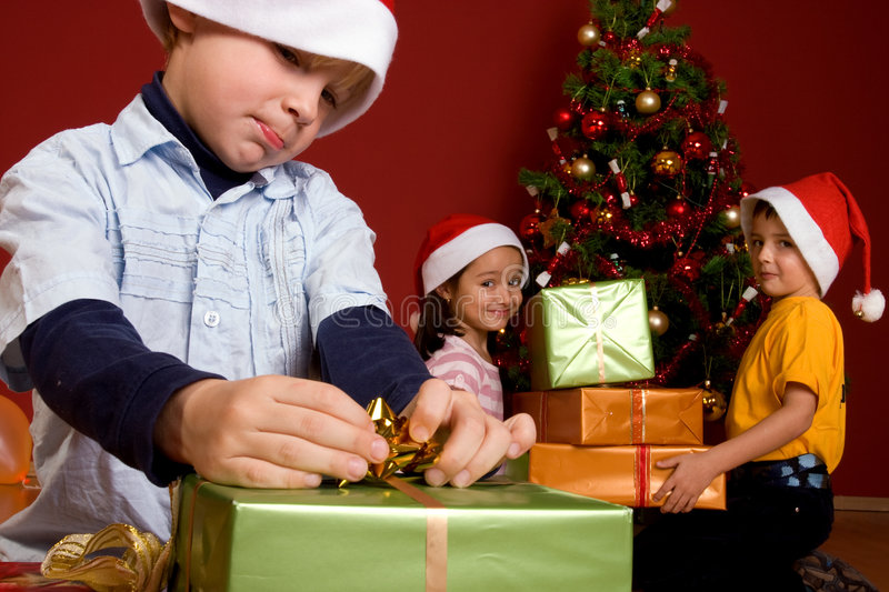 Young boy unwrapping Christmas gift stock photo