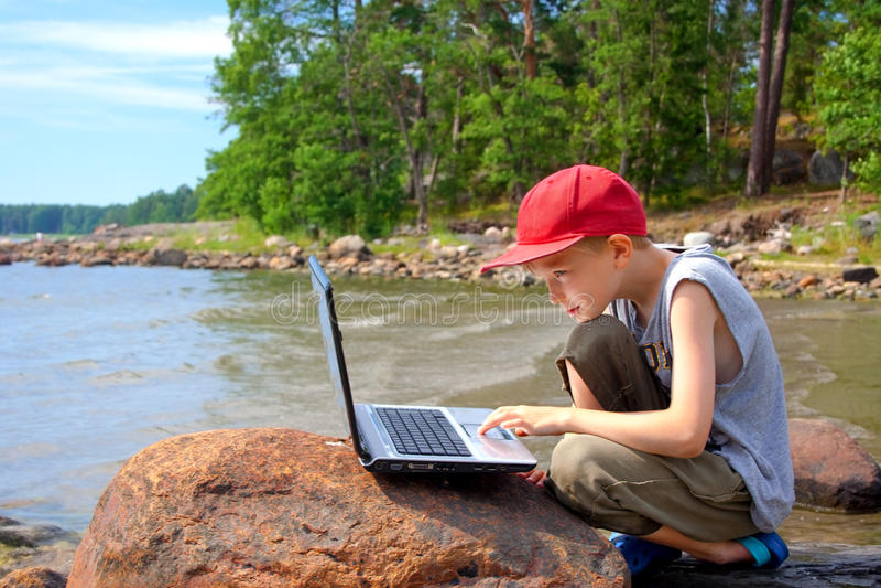 Young boy using a laptop stock photos