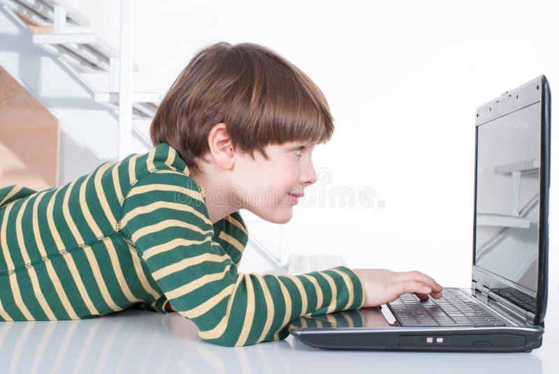 Young boy using a laptop royalty free stock photos