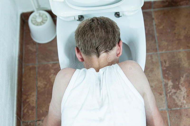Young boy vomiting into a toilet bowl. Young boy in a plain white t-shirt crouched on the floor vomiting into a toilet bowl, view from above stock image