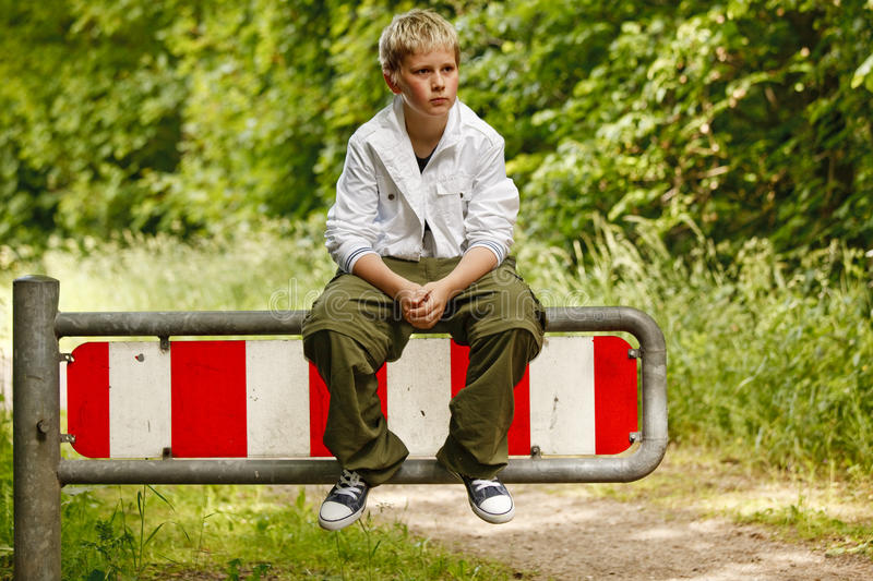 Young boy waiting on a traffic sign