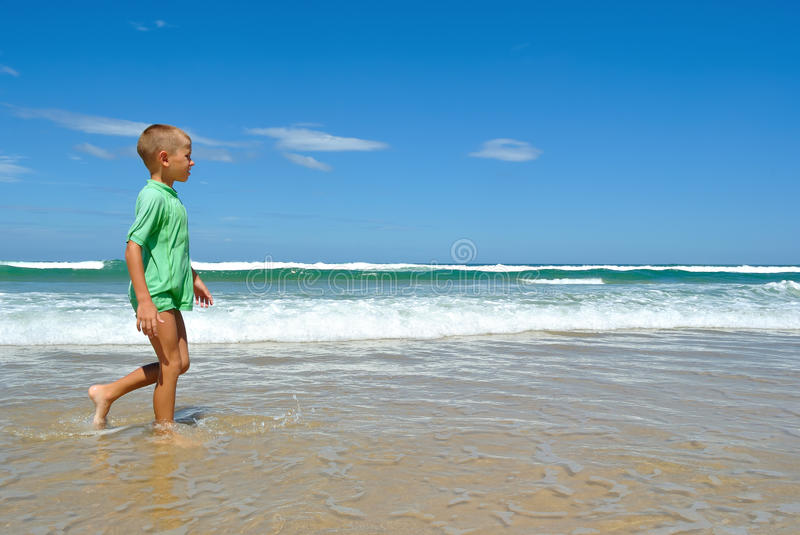 Young boy walking along the waters edge stock photo