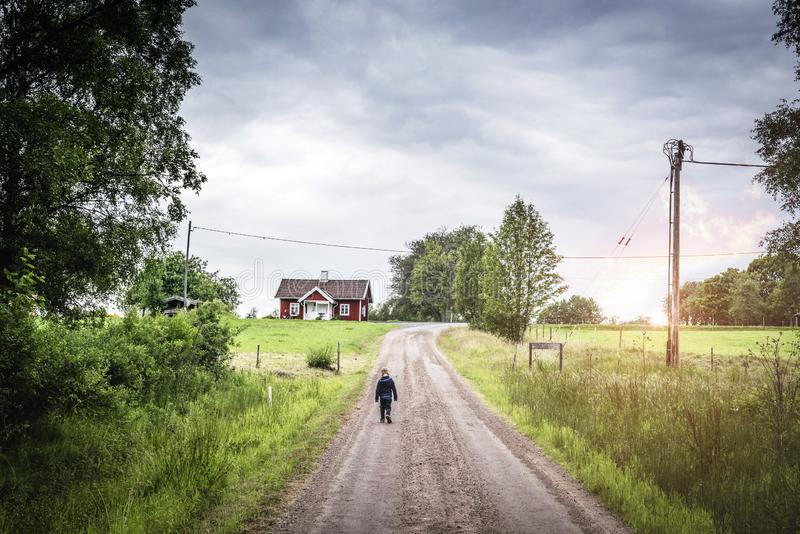 Young boy walking down a road in rural environment royalty free stock images