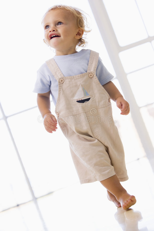 Young boy walking indoors smiling stock photography