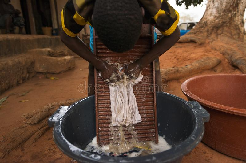 Young boy washing dirty clothes in a washing board and tub in the town of Nhacra in Guinea Bissau. West Africa royalty free stock image