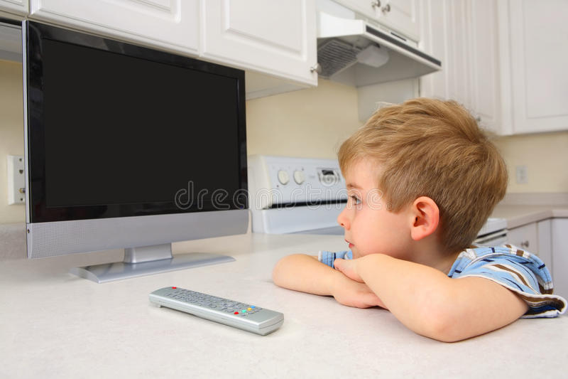 Download Young Boy Watching Tv In A Kitchen Stock Photo - Image: 9696438