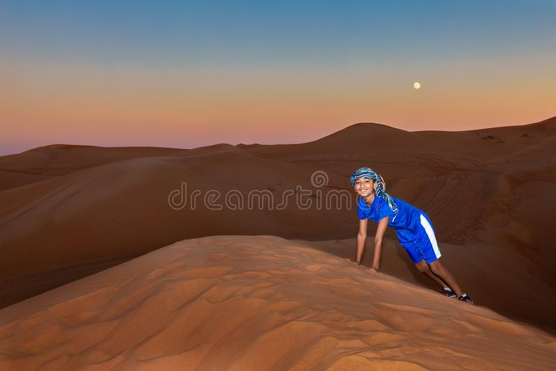 Young Boy Wearing Arabian Head Gear and Playing in the Sand Dunes at Sunset stock images