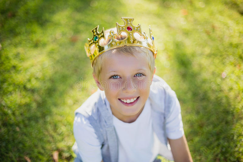 Young boy wearing a crown and smiling in park royalty free stock image