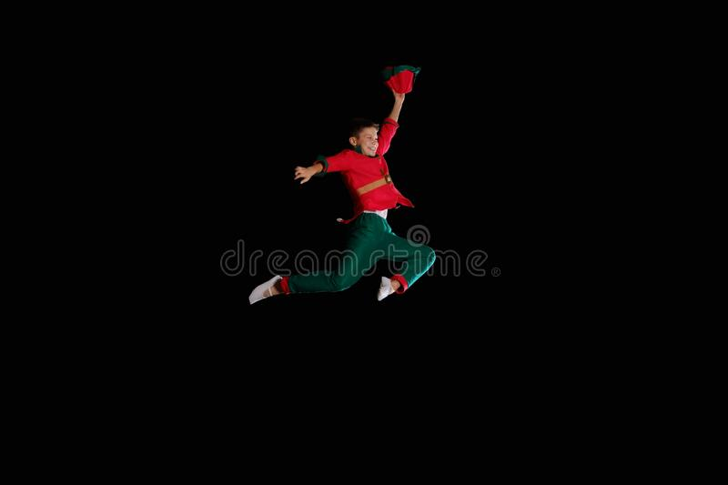 Christmas time, childhood, fairy tale. A young boy wearing elf costume is flying stock photo