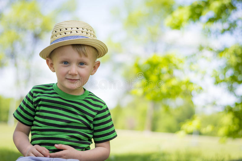 Young boy wearing a fedora at the park. Toddler having a blast at the park during the summer stock photos