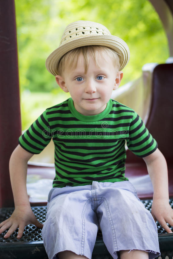 Young boy wearing a fedora sits on playground equipment. Toddler is having a blast at the park during the summer stock photos