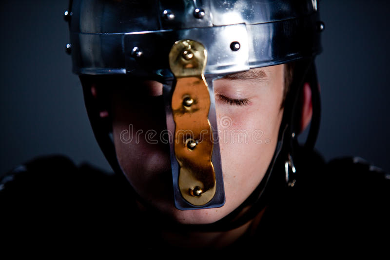 Young Boy Wearing Roman Soldier Helmet. Head and Shoulders Close Up of Young Boy with Closed Eyes Wearing Antique Soldier Helmet Made from Shiny Gold and Silver royalty free stock photos