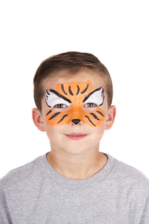 Young boy wearing tiger carnival face paint. Isolated on white royalty free stock photography