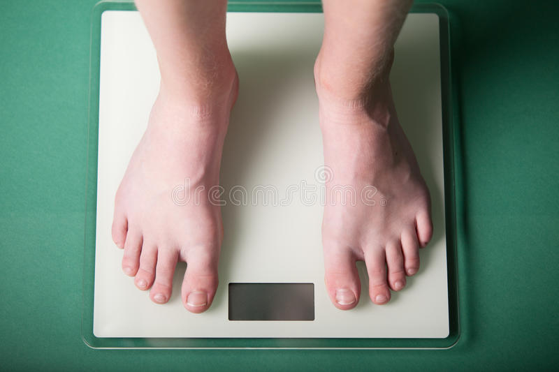 Young boy weighing himself on a scale. Young boy weighing himself on a bathroom scale to check his weight with a high angle view of his bare feet and a blank royalty free stock photos