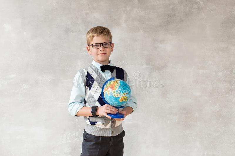 Young boy in white sweater and black trousers holds globe in hands and posing against gray wall stock images