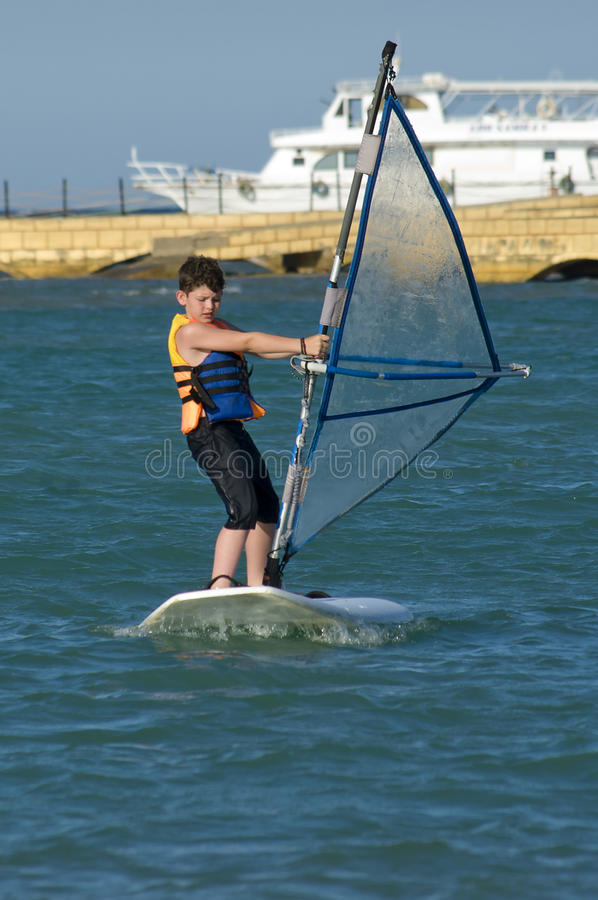 Young boy windsurfing and having fun royalty free stock photo
