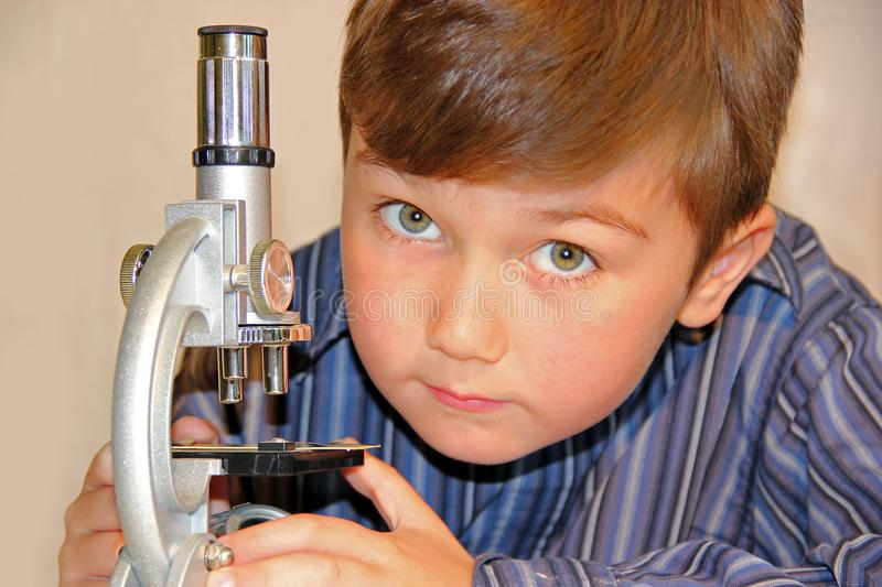 Young boy working with microscope royalty free stock photos