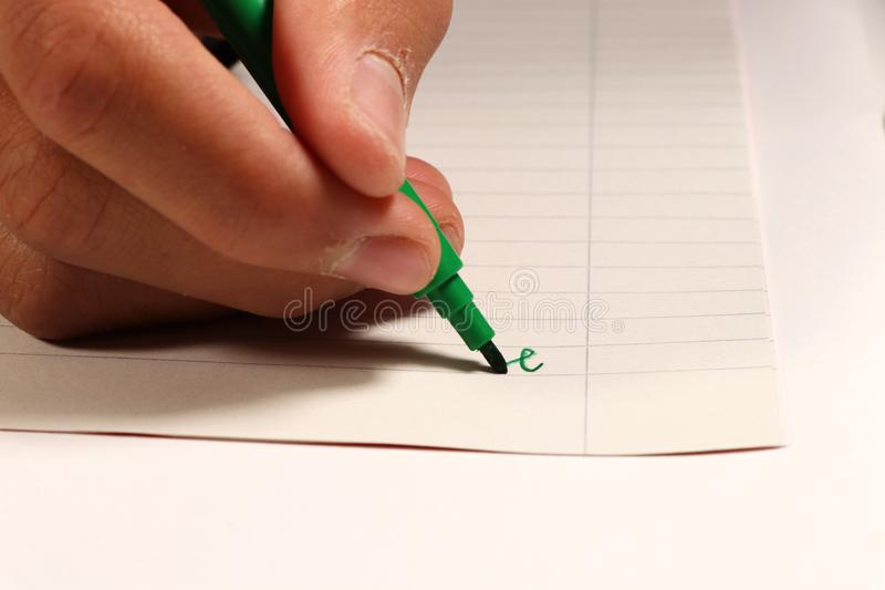 A young boy writing with green felt-tip pen a some word on english lesson at elementary school royalty free stock photo