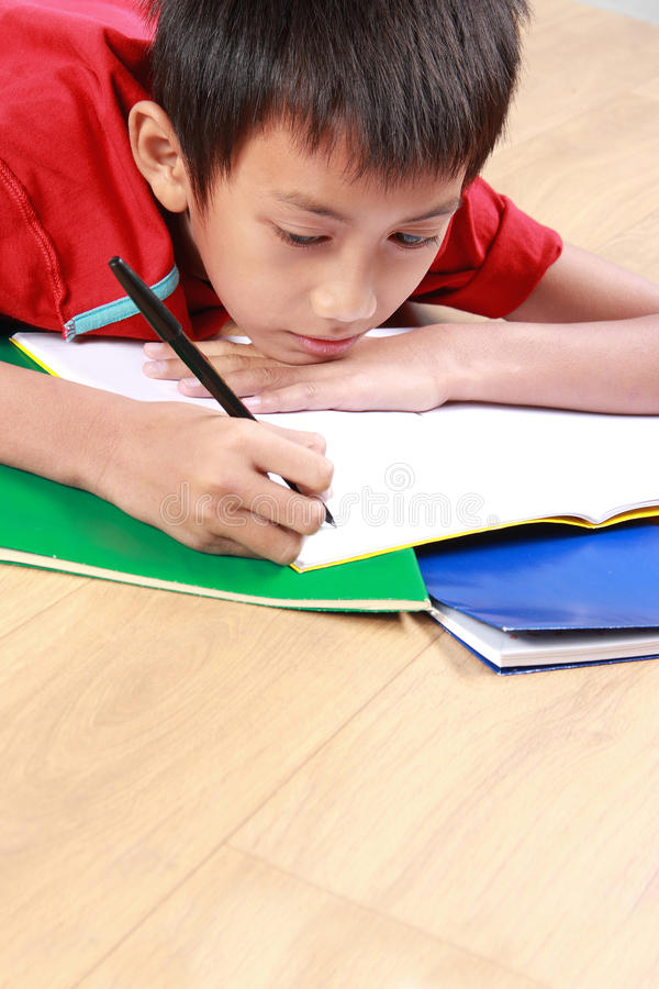 Young boy writing something on the book. Portrait of a stress young boy lay down writing something on the book stock photo