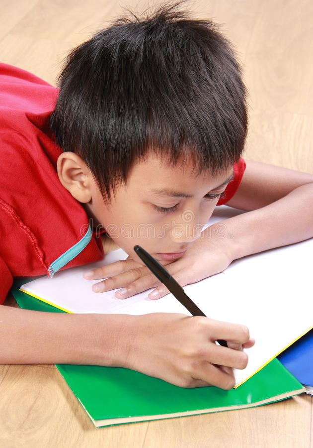 Young boy writing something on the book. Portrait of a stress young boy lay down writing something on the book royalty free stock image