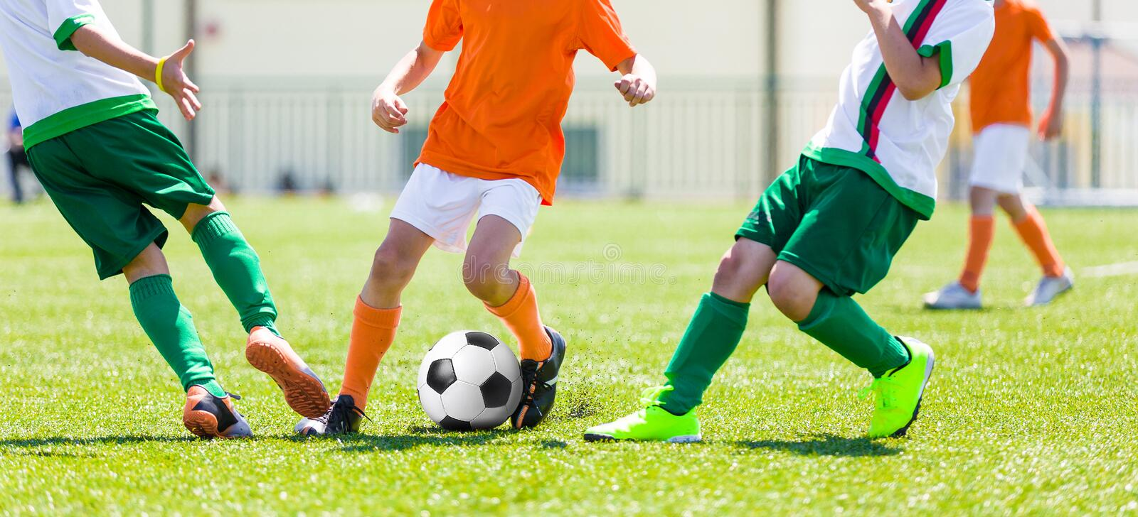Young boys children in uniforms playing youth soccer football game. Tournament. Horizontal sport background stock photo