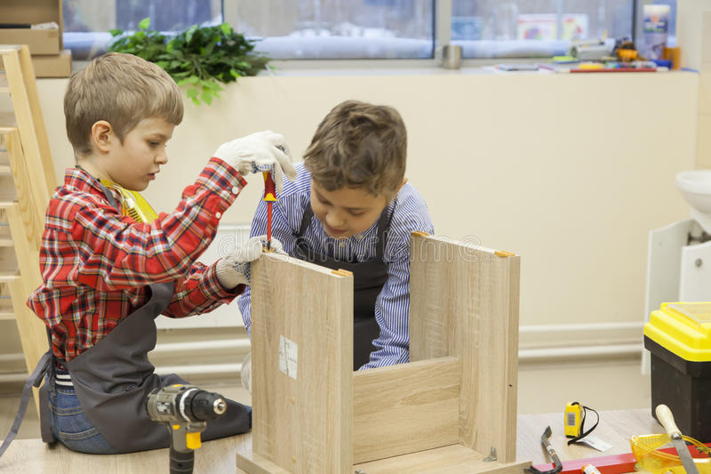 Young boys construct wooden stool royalty free stock images