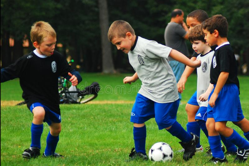 Boys in fierce competition. Young boys engage in fierce competition at a youth soccer game stock photo